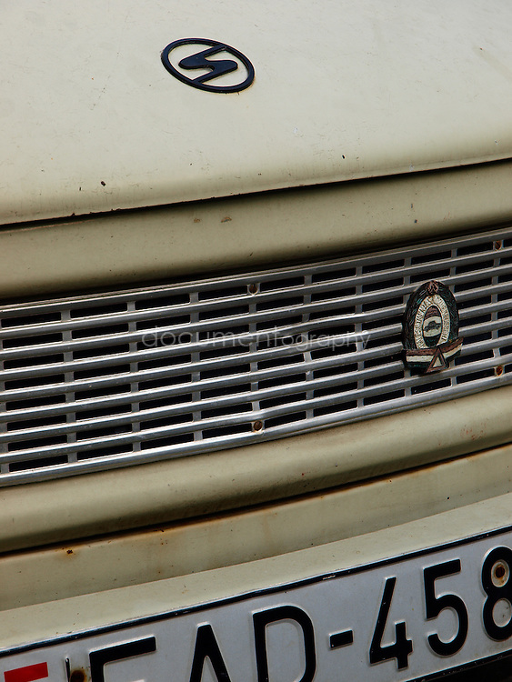 "Clse-up detail of a Trabant. The name Trabant means ""fellow traveler"" (Satellite) in Latin; the name was inspired by Soviet Sputnik. The cars are often referred to as the Trabbi or Trabi, pronounced with a short a. It was the most common vehicle in East Germany, and was also exported to countries both inside and outside the communist bloc. The main selling points were that it had room for four adults and luggage, and was compact, light and durable. Despite its poor performance and smoky two-stroke engine, the car has come to be regarded with affection as a symbol of the more positive sides of former East Germany and of the fall of communism, Budapest, Hungary."