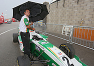 A man holds an umbrella over the Star Mazda car of Connor De Phillippi as rain falls before the start of the IZOD IndyCar Iowa Corn Indy 250 auto race at the Iowa Speedway in Newton, Iowa on Saturday, June 23, 2012.