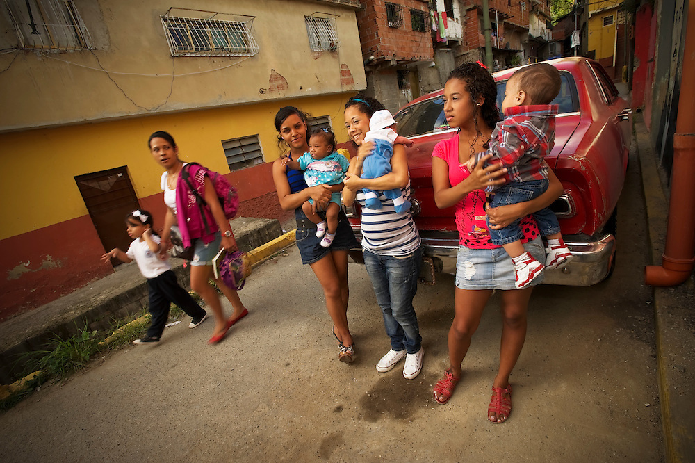 Teenage mothers, Diovile, Yanaifre and Keisy, talk with each other holding their babies in a slum in Caracas, Venezuela. Venezuela has the highest rate of teenage pregnancies in Latin America.  26 percent of babies are born to underage mothers.