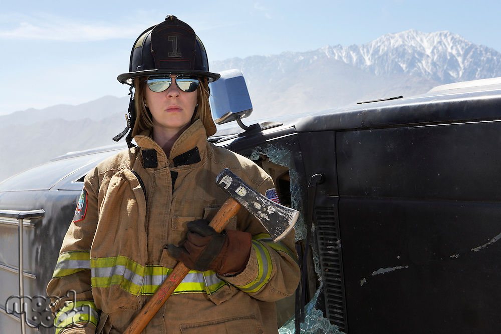 Portrait of female firefighter holding axe in mountains