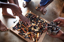 Club members reach for chess pieces at the Agape Church, where Phiona Mutesi, a 14-year-old chess prodigy, plays chess, inside Katwe, the largest of eight slums in Kampala, Uganda, Dec. 7, 2010. Mutesi lives in the slums of Uganda and is just now learning to read. But her instincts have made her a player to watch in international chess. Mutesi, a naturally talented chess player is coached by Robert Katende of Sports Outreach Ministry. The chess club meets at the Agape Church inside Katwe.