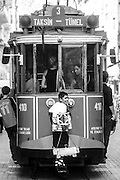 Young shoeshiner clings to the ancient tram that travels through Istiklal Caddesi, one of the main throughfares in Istanbul.