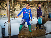"11 JUNE 2015 - MAHACHAI, SAMUT SAKHON, THAILAND:  Burmese migrant workers in Mahachai sell ice blocks to shrimp packers. Labor activists say there are about 200,000 migrant workers from Myanmar (Burma) employed in the fishing and seafood industry in Mahachai, a fishing port about an hour southwest of Bangkok. Since 2014, Thailand has been a Tier 3 country on the US Department of State Trafficking in Persons Report (TIPS). Tier 3 is the worst ranking, being a Tier 3 country on the list can lead to sanctions. Tier 3 countries are ""Countries whose governments do not fully comply with the minimum standards and are not making significant efforts to do so."" After being placed on the Tier 3 list, the Thai government cracked down on human trafficking and has taken steps to improve its ranking on the list. The 2015 TIPS report should be released in about two weeks. Thailand is hoping that its efforts will get it removed from Tier 3 status and promoted to Tier 2 status.       PHOTO BY JACK KURTZ"