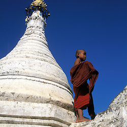 A novice monk among whitewashed spires of a monastery near Mandalay, Myanmar.