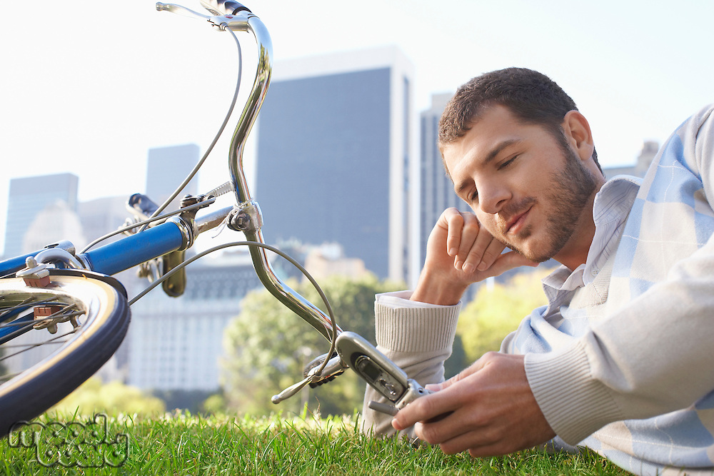 Man lying  on lawn in park looking at mobile phone close-up