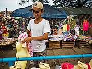 """25 OCTOBER 2015 - INSEIN, MYANMAR: A man sells women's clothes in Danyin Market (also known as Da Nyin) in Insein, Myanmar, about 90 minutes from Yangon. Vendors in the market sell just about everything people in the area need, but mostly it's a """"wet market"""" with fruits, vegetables and meats. Most people in Myanmar still do not have refrigerators in their homes, so people go to market almost every day.    PHOTO BY JACK KURTZ"""