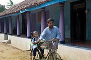 Father taking his daughter to school on the bar of his bicycle. Nagapattinam.<br /> Tamil Nadu. South India.