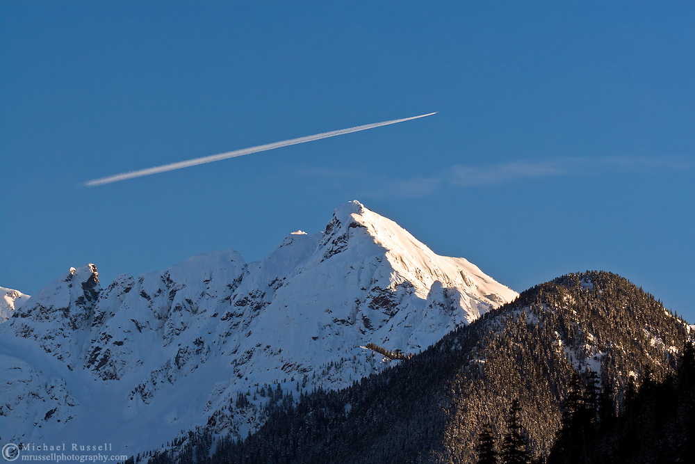 An airplane flies over Nodoubt Peak in North Cascades National Park, Washington State, USA.