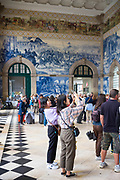 Tourists photographing famous azulejos traditional Portuguese blue and white wall tiles Sao Bento railway station in Porto, Portugal