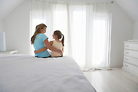 Mother and daughter sitting on bed in bedroom