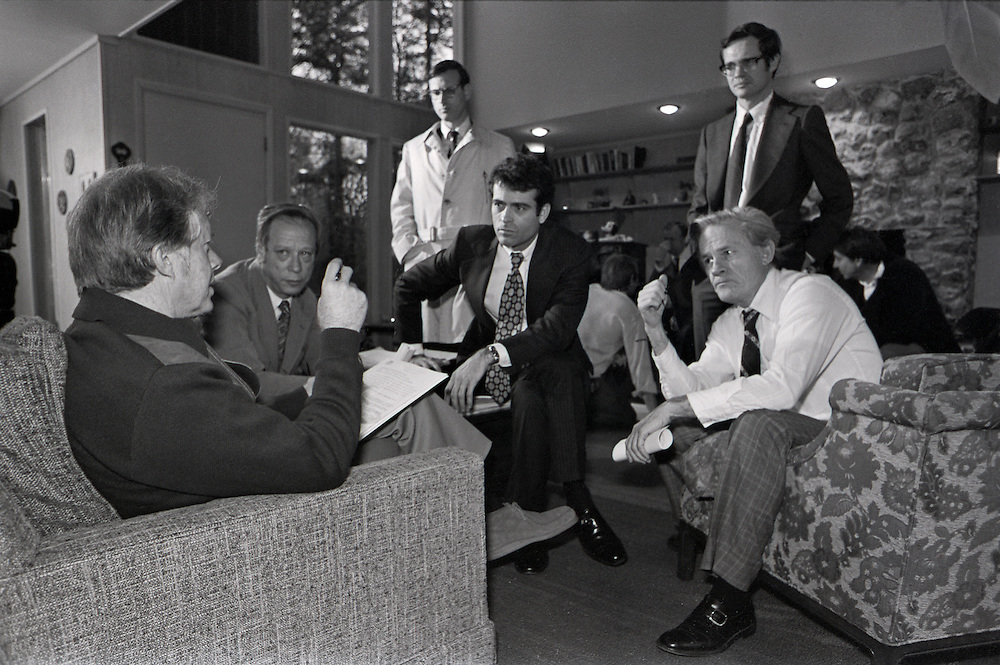 """January 1977 – Plains, Georgia)  President-elect Jimmy Carter talks with several his closest advisors and transition team members at the Carter's family retreat """"Pond House"""" just outside of the small south Georgia town of Plains. . Left to right are:  Michael Blumenthal, (Treasury Secretary nominee),  Stuart Eizenstat, (Chief Domestic Policy Advisor), Jack Watson, (Transition Director and later Chief of Staff),  Unidentified (dark hair, glasses, standing), Charles Schultze, (Chairman of the Council of Economic Advisors)."""
