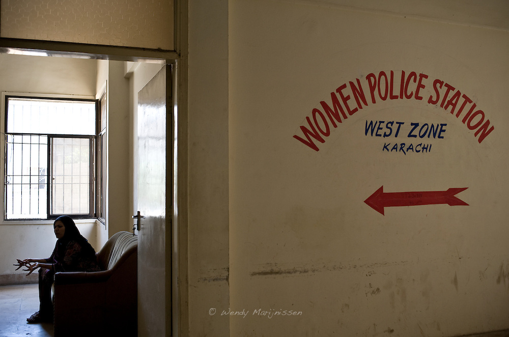 A sign points to the entrance of the West Zone Women's police station in Karachi. The objective for the station is to investigate cases of violence against women in order to ensure the women fair treatment of their cases. Sadly in reality the women police stations  lack any proper authority to help the women. Pakistan, 2011