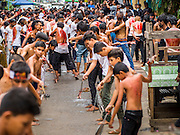 04 NOVEMBER 2014 - YANGON, MYANMAR: Burmese men flagellate themselves with chains and razors on Ashura in Yangon. The flagellation shows solidarity with Hussein and his family. Mogul Mosque is the principal Shia mosque in Yangon. Ashura commemorates the death of Hussein ibn Ali, the grandson of the Prophet Muhammed, in the 7th century. Hussein ibn Ali is considered by Shia Muslims to be the third imam and the rightful successor of Muhammed. He was killed at the Battle of Karbala in 610 CE on the 10th day of Muharram, the first month of the Islamic calendar. According to Myanmar government statistics, only about 4% of the population is Muslim. Many Muslims have fled Myanmar in recent years because of violence directed against Burmese Muslims by Buddhist nationalists.     PHOTO BY JACK KURTZ
