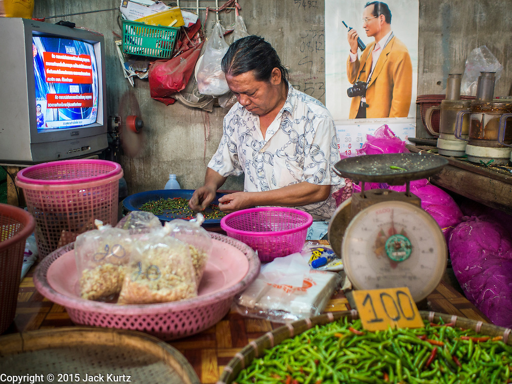 03 APRIL 2015 - CHIANG MAI, CHIANG MAI, THAILAND: A vendor sorts chilies in the market in Chiang Mai, Thailand. He is sitting under a portrait of Bhumibol Adulyadej, the King of Thailand.      PHOTO BY JACK KURTZ