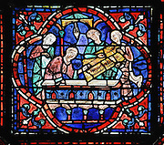 Inside the tomb, 2 unmarked coffins are found, but Julienne recognises her husband's, which she indicates. Two men remove a gold coffin. Section of the Misunderstanding, 1220-25, from the Life of St Stephen and transferral of his relics window in the ambulatory of Chartres Cathedral, Eure-et-Loir, France. This window, unusually dominantly red in colour, tells the story of the life of St Stephen, the first Christian martyr, who died c. 36 AD and whose relics are held at Chartres. It is situated in the chapel dedicated to martyrs. Chartres cathedral was built 1194-1250 and is a fine example of Gothic architecture. Most of its windows date from 1205-40 although a few earlier 12th century examples are also intact. It was declared a UNESCO World Heritage Site in 1979. Picture by Manuel Cohen