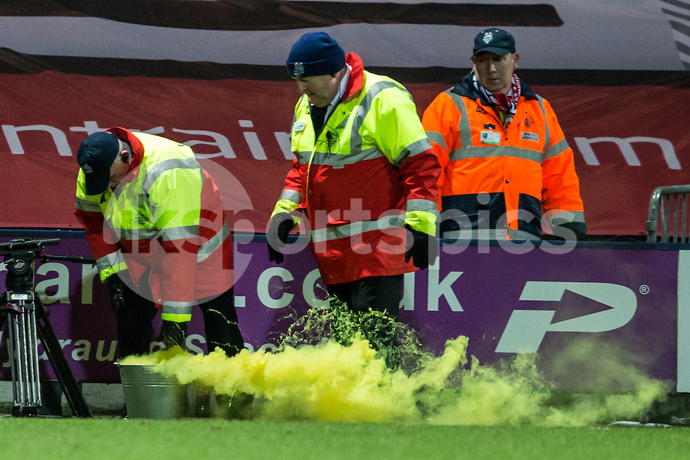 Preston Stewards put out a flare thrown from the crowd after Scott Laird had put Preston North End in the lead against Manchester United during the The FA Cup match between Preston North End and Manchester United at Deepdale, Preston, England on 16 February 2015. Photo by James Williamson.