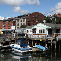 A view of the Portland, Maine, USA, waterfront. The restaurant in the foreground is the Portland Lobster Co., a popular waterfront eatery next to Long Wharf pier from which scenic cruises of Casco Bay depart.