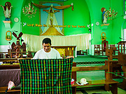 28 NOVEMBER 2017 - YANGON, MYANMAR: A man sleeping in the sanctuary at St. Francis of Assisi Church in Yangon shakes out his longyi (traditional Burmese sarong) after he woke up Tuesday morning. He said he is going to the papal mass Wednesday. About 1,500 people are camping at the church before the papal mass at Kyaikkasan Sports Ground, about three kilometers from the church.    PHOTO BY JACK KURTZ