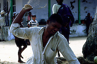 TAMIL NADU, MARCH 1994.A man is angrily throwing sand around him while people observe him from the distance.