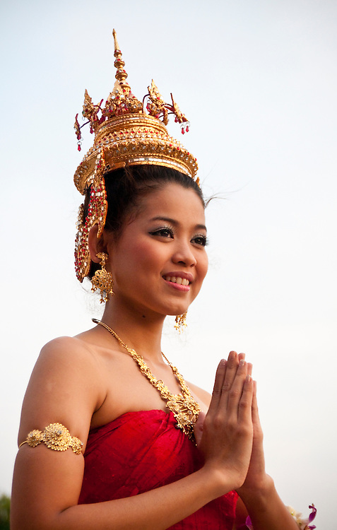 "Young Thai woman in traditional costume with golden crown and jewelry and hands together in traditional ""wai"" greeting; at Siam Niramit, Bangkok, Thailand."