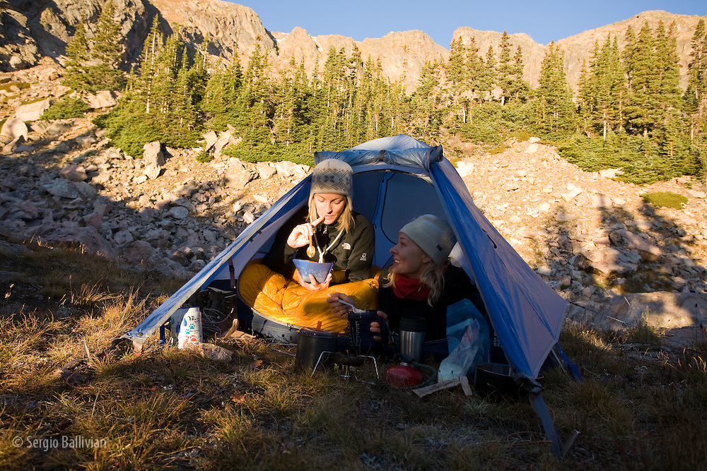 Two girl friends eat breakfast while still in their sleeping bags and tent while backcountry camping.
