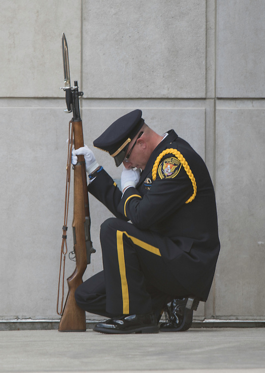 Photo by Michael R. Schmidt  Antioch, IL September 7, 2015<br />A member of the Honor Guard pauses and kneels during memorial services for Police Lieutenant Charles Joseph Gliniewicz were held at  Antioch Community High School on Monday, September 7, 2015. Gliniewicz, a 30-year veteran was shot and killed last week in the line of duty.