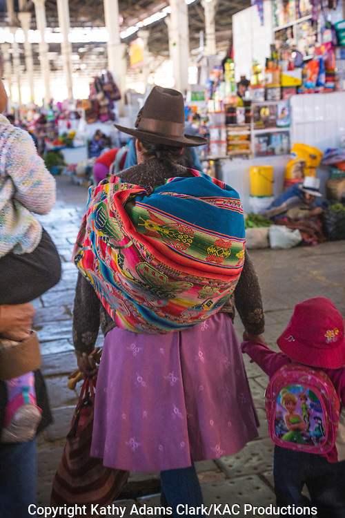Lady in traditional dress in Cusco, Peru. Hat denotes village or region. with little child wearing a pink back pack.