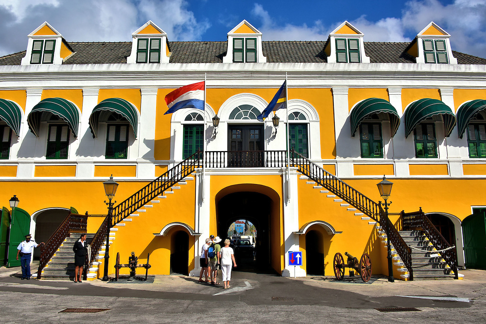 Fort Amsterdam Inner Courtyard in Punda, Eastside of Willemstad, Curaçao  <br /> Shortly after the Netherlands overthrew the Spanish in 1634, the Dutch West India Company began building a fortress on the eastern shore of the Sint Anna Bay. Fort Amsterdam saw military action by the British in 1804 and fell to Venezuelan soldiers in 1929.  Notice the two cannons in the inner courtyard that once protected the city. This beautiful old citadel now serves as the home of the island's governor plus contains other government offices.