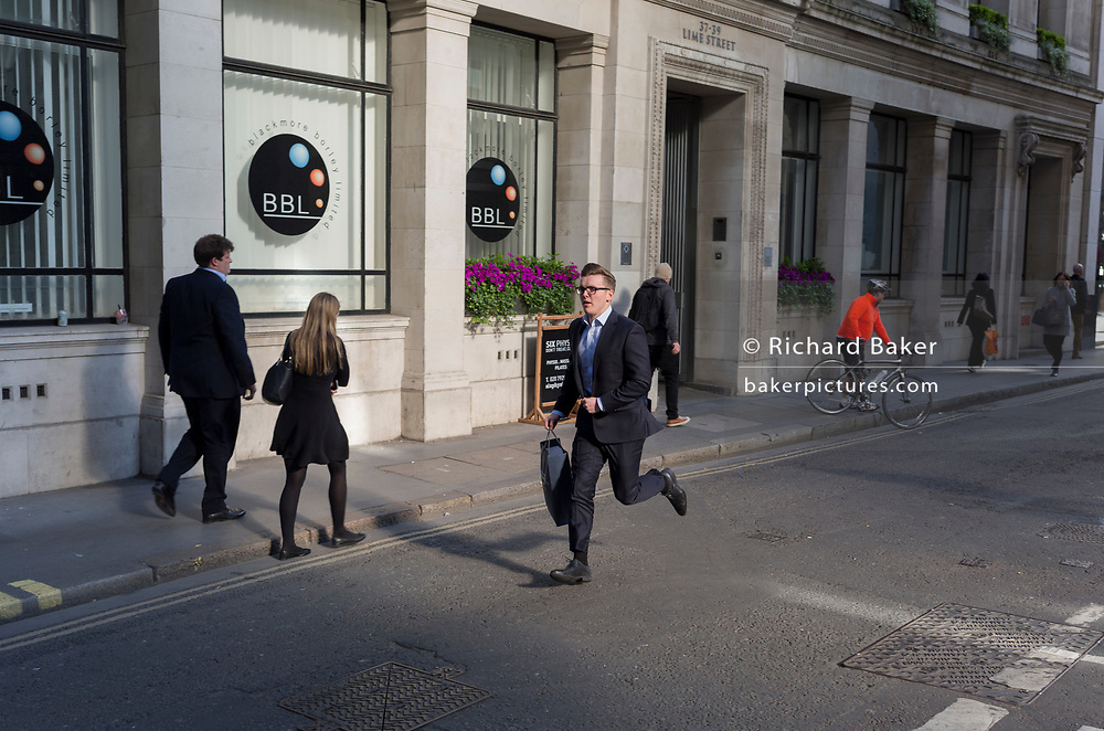 A rushed businessman on Lime Street, hurries along the street in a run, on 10th May 2017, in the City of London, England.