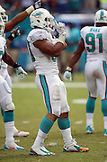 Miami Dolphins defensive end Olivier Vernon (50) celebrates after sacking New England Patriots quarterback Tom Brady (12) for a loss of 7 yards and forces a punt in the fourth quarter during the NFL week 1 regular season football game against the New England Patriots on Sunday, Sept. 7, 2014 in Miami Gardens, Fla. The Dolphins won the game 33-20. ©Paul Anthony Spinelli