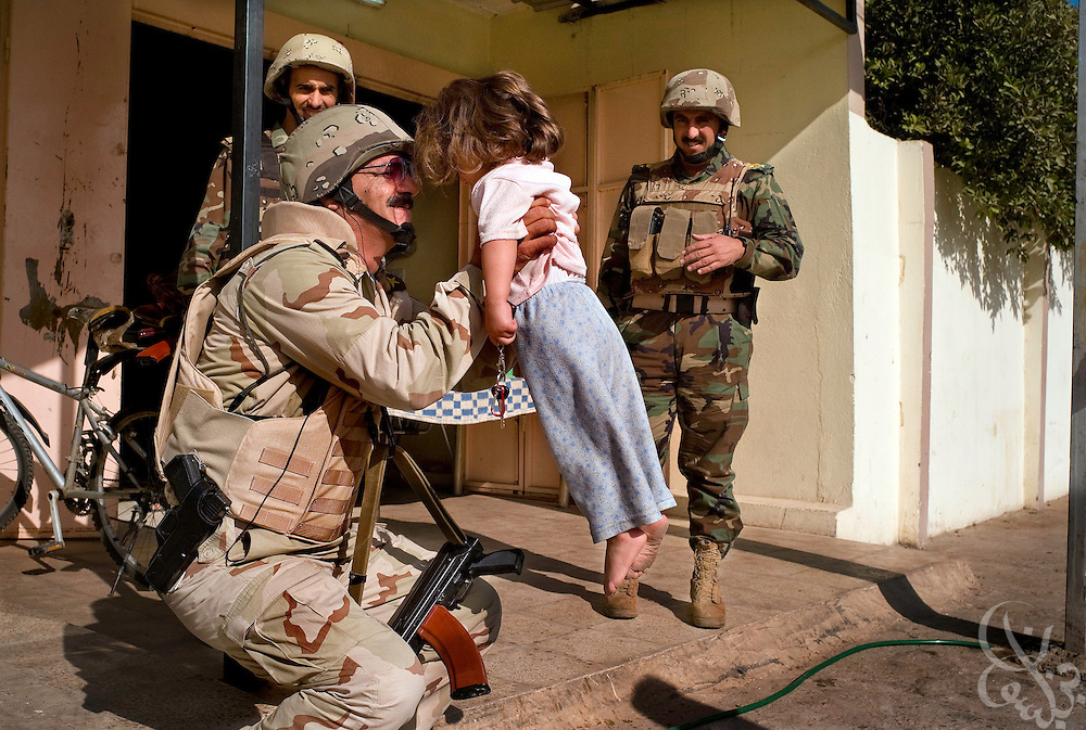 Iraqi Army 2nd Division Brigadier General Nuradeen Tatar Khan Hirki playfully lifts an Iraqi girl during a joint U.S.-Iraqi neighborhood sweep to search for weapons caches October 18, 2007 in Mosul, Iraq. Iraqi security forces in Mosul have taken over the day to day tasks of securing the city, allowing U.S. forces in the area to pull back and reduce its presence.