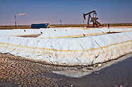 Fracking site with  dried toxic waste in a frack pond in Big Spring Texas, part of the Permian Basin where fracking is done for oil.