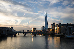 © Licensed to London News Pictures. 13/09/2016. London, UK.  Buildings in sight of The Shard reflect the sunrise on the River Thames. Another warm sunny day is expected with hot temperatures predicted in the south east.Photo credit: Peter Macdiarmid/LNP