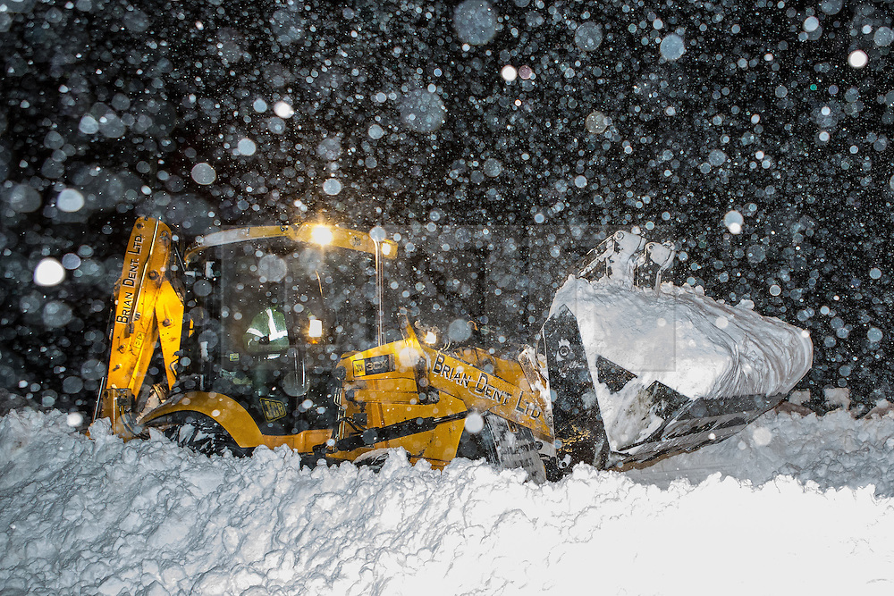 © Licensed to London News Pictures . 24/03/2013 . Burnley , UK . A JCB operator works to scoop and plough through a large snow drift to clear Halifax Road as wind blows snow from its scoop . The operator is working an 18 hour shift . Snowdrifts are making roads impassable around Burnley overnight (23rd/24th March) as high winds blow snow across roads . Plummeting temperatures and treacherous conditions are reported to have taken the life of a man named locally as Gary Windle . Lancashire Police reported finding a 27 year old man dead in deep snow yesterday (23rd March) afternoon . Photo credit : Joel Goodman/LNP