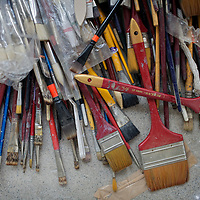 "A pile of brushes in the studio of Subodh Gupta, contemporary artist. ..Gupta's most celebrated sculptures are constructed from common domestic items including the steel pots and pans that are a feature every Indian home. Of the kitchen-ware that forms the basis of his work, Gupta says,..""The poor, the middle class and the rich use it at home. In this country, how many people have the utensils but they starve because there is no food?""..Gupta was brought up, one of six children, to a railway-worker father in a north Indian village. ..Gupta's work fetches such huge sums of money. Two versions of his Mind Shut Down, modeled on the human skull and constructed entirely of steel kitchen utensils recently sold for EUR1 million each...Photo: Tom Pietrasik.Gurgaon, Haryana. India. .June 26th 2009"