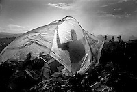 A man shakes out a sheet of plastic he collected from the dump that he will use as rain protection in his home in nearby Cite Soleil.