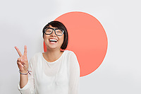 Portrait of cheerful young woman gesturing peace sign against Japanese flag