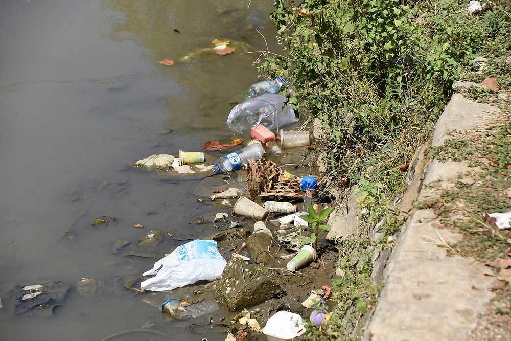 Rubbish flowing down a small river in Indonesia, next to a slum area called the painted village