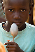 A girl holds spoon next to her face outside the Ying Anglican Primary School in the Savelugu-Nanton district, northern Ghana on Monday June 4, 2007. Through a partnership between parents and Christian Relief Services (CRS) children a provided with a meal every day. According to one of the teachers, this alone is responsible for a 40 percent increase in attendance.