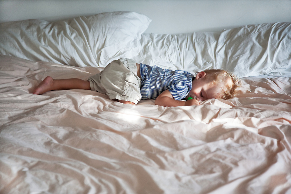 1 year old baby boy in sleeping in adult bed face down