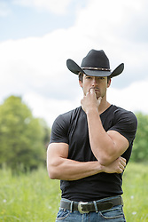 All American handsome cowboy outdoors on a ranch