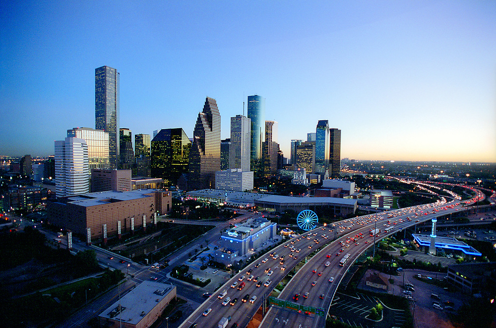 Aerial evening view of Houston, Texas skyline from the Northwest with traffic on freeway in the foreground.