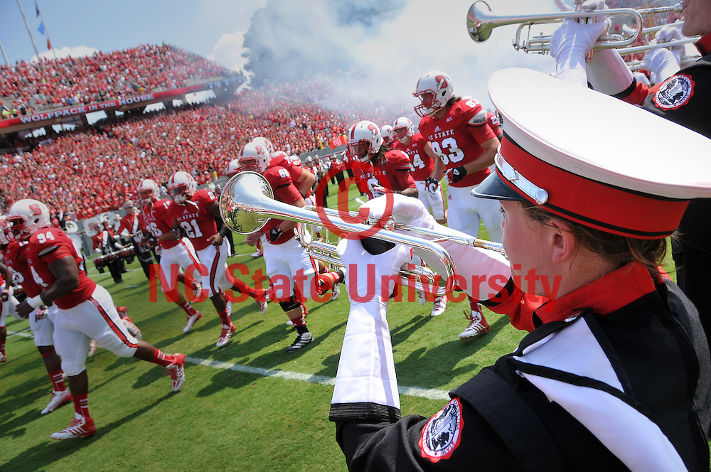 Marching band members play as the football team takes the field.