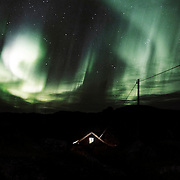 Northern Lights dancing over the house. Stories circulate on the island of old kæiller (ancestors) within the walls.