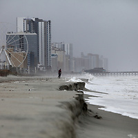 A man walks along an eroded stretch of the Grand Strand near the SkyWheel in Myrtle Beach as Tropical Storm Florence continued to kick up surf Saturday, Sept. 15, 2018. Andrew Knapp/Staff