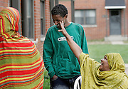 Nimo Buni, Ismail Ismail's sister's mother-in-law, jokes around with Ismail while his mother Fadumo Ahmed Ali, left, watches from their front porch on Monday, Oct. 2. The 16-year-old East High School sophomore was reunited with his family a year ago after he was separated while the family was fleeing Somalia when he was two.
