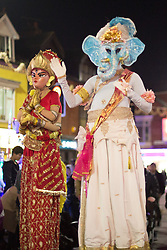 "© Licensed to London News Pictures. 01/11/2015. Leicester, UK. More than 35,000 people were estimated to have attended the annual Diwali light switch-on which took place along the named ""Golden Mile"" in Belgrave Road, Leicester. Pictured, Figures on stilts make their way along the Belgrave Road ready for the lights switch-on. Photo credit : Dave Warren/LNP"