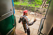 15 JUNE 2013 - YANGON, MYANMAR:  A vendor hops off the Yangon Circular Train at a stop. Yangon Circular Railway is the local commuter rail network that serves the Yangon metropolitan area. Operated by Myanmar Railways, the 45.9-kilometre (28.5 mi) 39-station loop system connects satellite towns and suburban areas to the city. The railway has about 200 coaches, runs 20 times and sells 100,000 to 150,000 tickets daily. The loop, which takes about three hours to complete, is a popular for tourists to see a cross section of life in Yangon. The trains from 3:45 am to 10:15 pm daily. The cost of a ticket for a distance of 15 miles is ten kyats (~nine US cents), and that for over 15 miles is twenty kyats (~18 US cents). Foreigners pay 1 USD (Kyat not accepted), regardless of the length of the journey.     PHOTO BY JACK KURTZ
