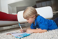 Elementary age boy writing in book while lying down on rug in house