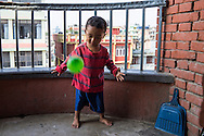 Sujal Tamang (2) plays with a ball on the balcony of his aunt's apartment on the 5th floor in Jorpati, Kathmandu, Nepal on 2 July 2015. Sujal was buried under the rubble of his collapsed house for 36 hours before rescuers found him injured with a broken leg next to his mother who was killed on the spot. Photo by Suzanne Lee for SOS Children's Villages